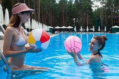 プールで遊ぶ女性とビーチボール