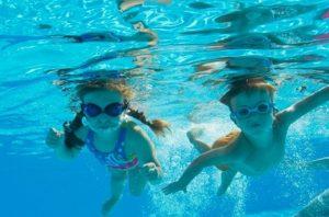 プールで潜って泳ぐ男の子と女の子